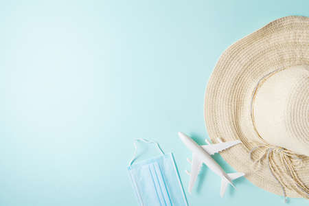 Optimistic coronavirus vacation concept. Summer 2021 vacation and travel background with sun hat, medical mask, airplane flat lay. Waiting spring or summer time.