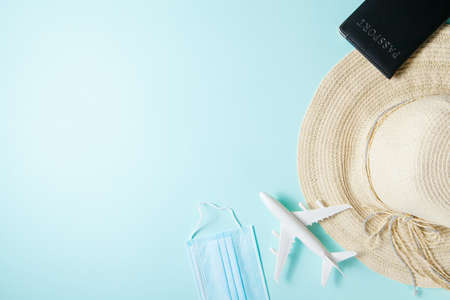 Optimistic coronavirus vacation concept. Summer 2021 vacation and travel background with sun hat, medical mask, passport, airplane flat lay. Waiting spring or summer time. Standard-Bild
