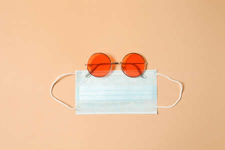Red round sunglasses with medical mask on brown background. Banner template with goggles, face mask and copy space. Global quarantine and social distancing during summer time.