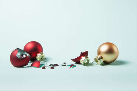 Broken red christmas ball and safe two on light blue background. Choose between glass balls or plastic balls concept.