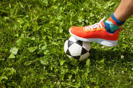 Horizontal image of soccer ball with foot of player touching it. Small soccer ball with foot wearing colorful shoes.