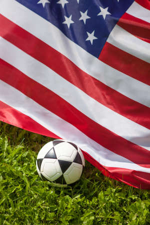 Soccer ball with flag of America on green grass background.