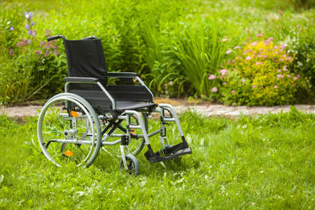 Empty wheelchair in the garden or in the park. Wheelchair in the grass in the garden.