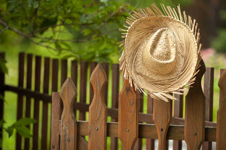 A yellow straw cowboy hat resting on a fence post with farmland in the background.