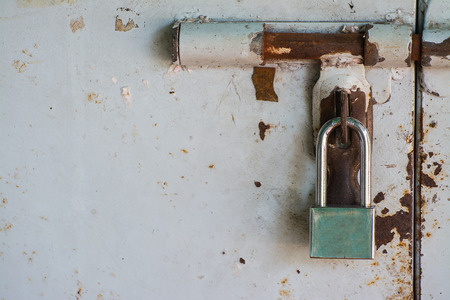 new padlock on old rusty white door 스톡 콘텐츠