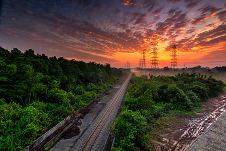 Railroad against beautiful burning sky at sunrise. Industrial landscape with railroad, colorful blue sky with burning clouds, sun, trees and green grass. Railway junction.