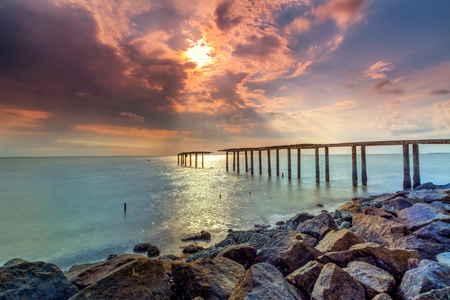 A long Exposure Picture Of abandoned old jetty with  burning sunset as background