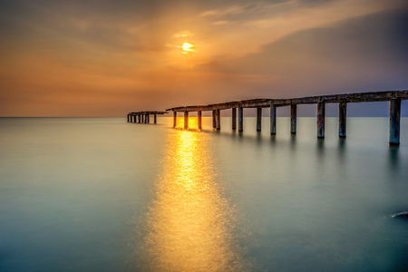 A long Exposure Picture Of abandoned old jetty with cloudy before burning sunset as background