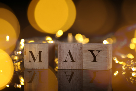 Month Concept, front view shows wooden block written May with light and bokeh background