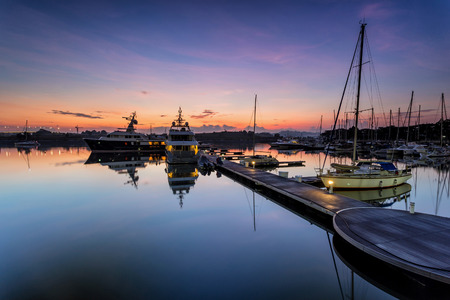 A majestic sunrise with boat resting near   the dock as foreground at Putri Harbour, Iskandar Malaysia.
