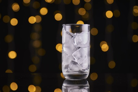 A glass of ice cube with bokeh background