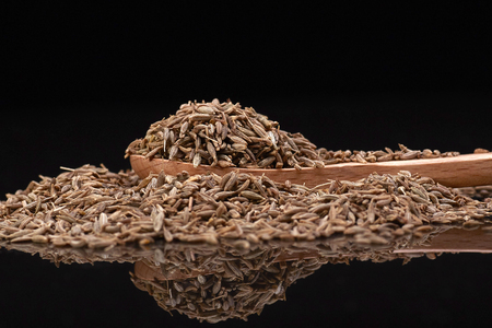 Cumin seed  over Black background with wooden spoon Stock Photo