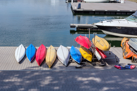 Colorful fiberglass kayaks tethered to a dock as seen from above