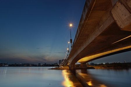 A long exposure picture of beautiful burning sunset and blue hour  under the bridge