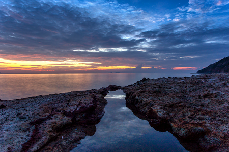 A long exposure picture Beautiful Scenery cloudy Sunset With Stone and wave As Foreground
