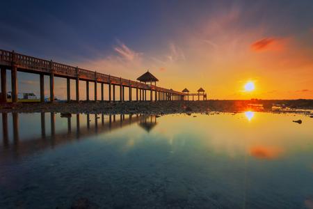 Ein Langzeitbelichtungsbild eines majestätischen Sonnenaufgangs mit einem Steg als Hintergrund bei Tanjung Balau, Johore Standard-Bild