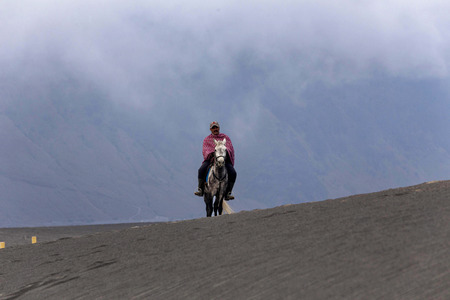 BROMO, INDONESIA - May 9 ,.2018. Unidentified local people or Bromo Horseman riding horse  at the mountainside of Mount Bromo, Semeru, Tengger National Park, Indonesia. 報道画像
