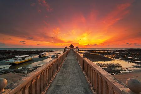 Ein Langzeitbelichtungsbild eines majestätischen Sonnenaufgangs mit einem Steg als Hintergrund bei Tanjung Balau, Johore