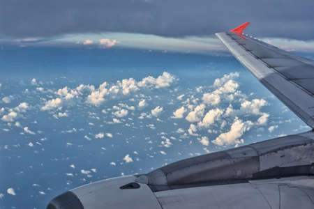 The passenger plane transports passengers in the air, looking out from the glass window of the plane while traveling, and the wing flies in the beautiful clouds of the sky.