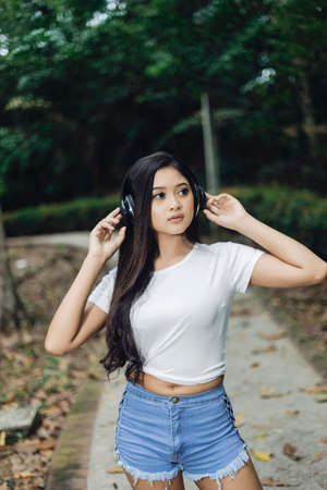 Pretty sporty woman jogging at park and using the headphone