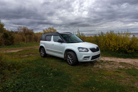 Universal white crossover car parked for travelers on the territories of coastal reserves in the Pskov region, west of the Izborsk Valley, Russia. Fishing, Hunting and Tourism