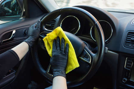 Cleaning car interior from coronovirus and pandemic with disinfectant fluid. Hands in rubber protective gloves wipe the car inside to protect against viral diseases Banque d'images