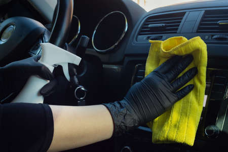 Cleaning car interior from coronovirus and pandemic with disinfectant fluid. Hands in rubber protective gloves wipe the car inside to protect against viral diseases Imagens