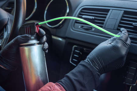Cleaning the climate system and air conditioner of a car from a coronovirus and a pandemic with a disinfectant fluid. Hands in rubber protective gloves wipe the car