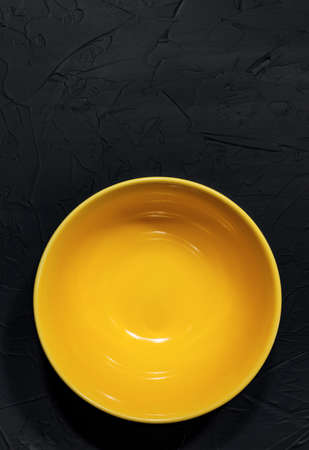 Yellow ceramic plate on a black background handmade in the loft or grunge style. Creating a cafe or diner, view from the top