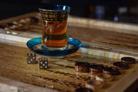 Board games wooden board of backgammon (tawla). Traditional oriental cup of tea and checkers