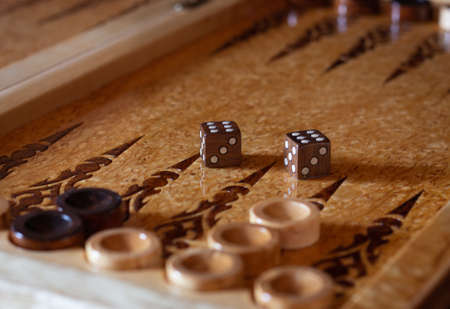 Board games wooden board of backgammon (tawla). Close-up details and checkers