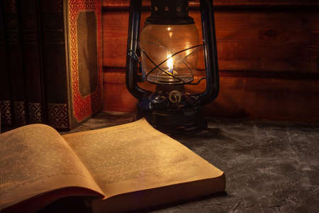 Reading a book in the light of an old hand-held kerosene lamp glows softly in a dark room on the table. Vintage style. The light in the darkness. Atmospheric photo in the loft style.