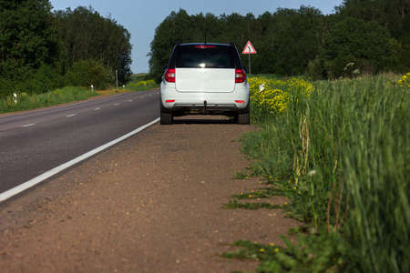 A modern white car sits at the edge of the road next to a green field while traveling and looking for new routes. Outdoor weekends, local travel and summer trips