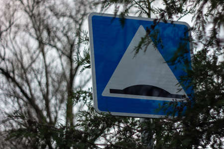 A road sign hidden in foliage to indicate an artificial obstacle in urban areas