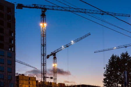 Close-up of a construction crane in the light of night lights on a modern site while working in new buildings. Night city landscape. Development concept