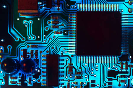 Close-up of a modern blue printed circuit board (PCB) with stripes of conductors between a transistor and an electronic equipment processor.