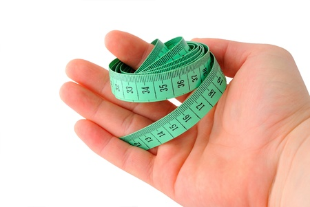 handbreadth: Green inch tape clutch in palm on white background. Stock Photo