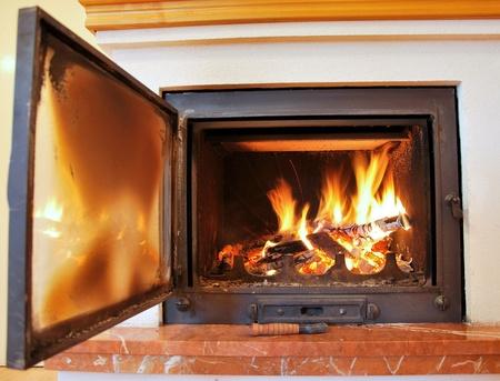 Indoor fireplace with open door. Stock Photo