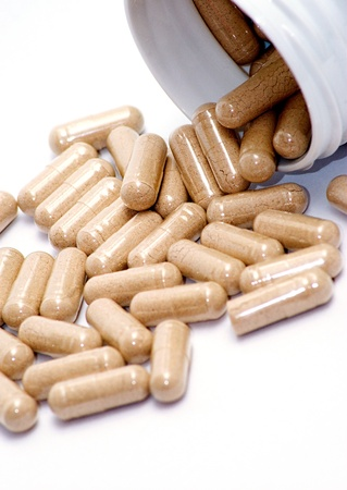 Closeup image of brown pills - roughage on the white background.