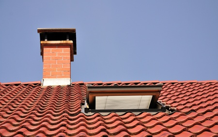 dormer: Red roof with chimney made from tiles and one dormer.
