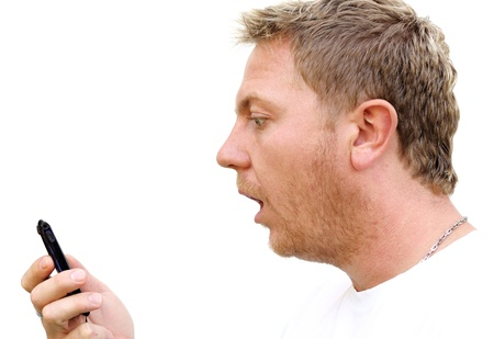 highkey: Young man gape at his mobile phone. Stock Photo