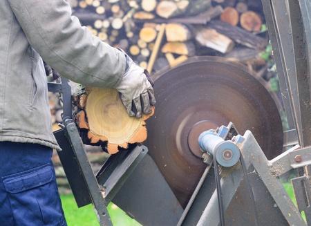 Man sawing wood on the circular saw. photo