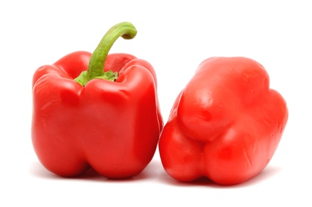 Two red peppers placed on the white background. photo