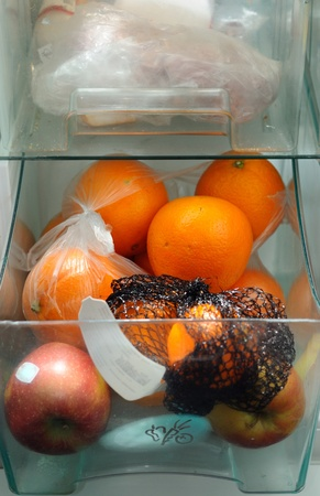 Refrigerator drawer full of oranges and apples. photo