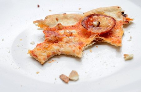 The remains of salami pizza on the white dish