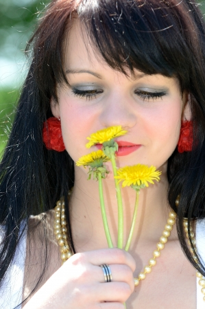 Young girl is sniffing the flower  photo
