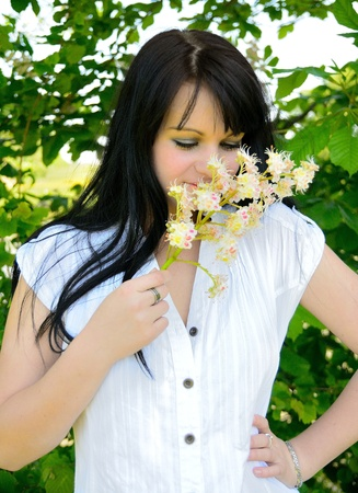 Young happy girl is smelling the flower  Stock Photo - 13779607