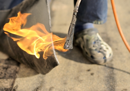 Man working with burner and insulation on the roof