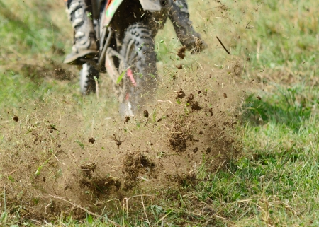 Flying mud from moving motorcycles enduro wheel  photo
