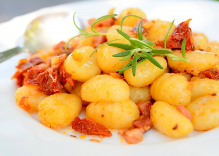 Gnocchi with tomatoes, bacon and onion on the white plate  스톡 콘텐츠
